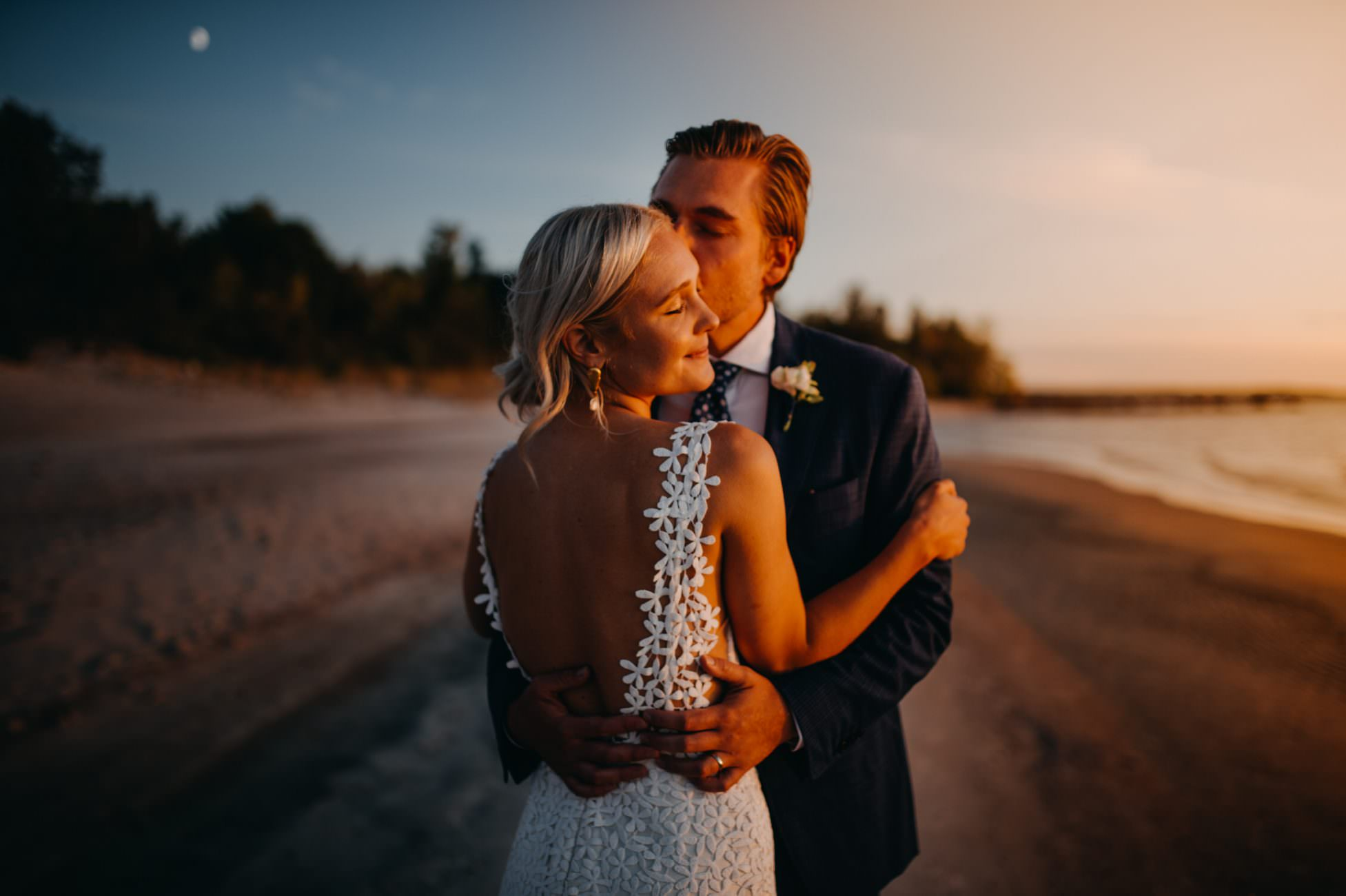 bride and groom dancing at sunset at Victoria Beach photographed by Calgary intimate wedding photographer